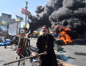 An Orthodox priest gestures with a stick as Maidan self-defence activists clash Kiev-1 volunteer battalion in Kiev. (Photo by Sergei Supinsky/AFP/Getty Images)